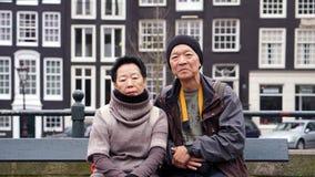 Asian senior couple travel to Amsterdam together. Taking photo w Royalty Free Stock Photo