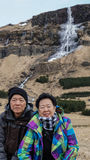 Asian senior couple travel to Icealand, Europe trip after retire. Ment. High waterfall frozen amazing landscape Royalty Free Stock Images