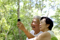 Asian senior couple using cell phone in nature Royalty Free Stock Images