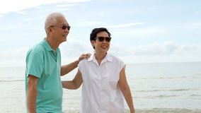 Asian senior couple walking together on beach by the sea Stock Images