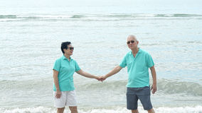 Asian senior couple walking together on the beach by the sea Stock Photography