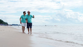 Asian senior couple walking together on the beach by the sea Stock Image