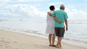 Asian senior couple walking together on beach by the sea Stock Photo