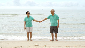 Asian senior couple walking together on beach by the sea Royalty Free Stock Images