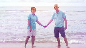 Asian senior couple walking together on the beach by the sea Royalty Free Stock Images