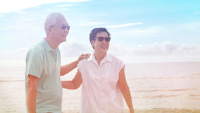Asian senior couple walking together on beach by the sea Royalty Free Stock Photography