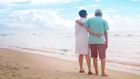 Asian senior couple walking together on beach by the sea Royalty Free Stock Image