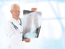 Asian senior doctor checking on x-ray image Stock Photo