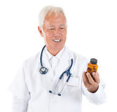 Asian senior doctor holding a bottle of pills Royalty Free Stock Image