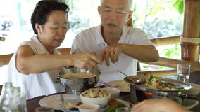 Asian senior elderly couple talking care each other at meal  time stock video