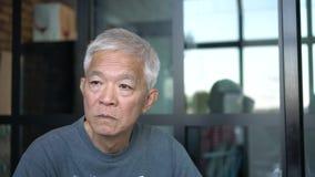 Asian senior elderly man thinking window glass background