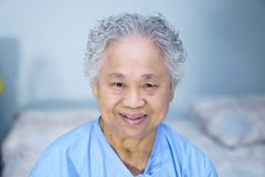 Asian senior or elderly old lady woman patient smile bright face while sitting on bed in nursing hospital ward. Healthy strong medical concept royalty free stock images