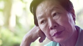 Asian senior elderly woman worry expression thinking about life stock image