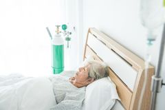 Senior female patient sleeping on bed in hospital Stock Images