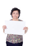 Asian senior female standing with empty horizontal blank paper i Stock Image