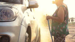 Asian senior female washing Family car with water tube,Slow motion shoot. With ,120 Fps By Sony A6300 stock video