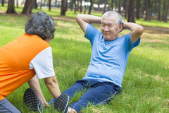 Asian senior grandfather doing sit-ups in the park Royalty Free Stock Photography