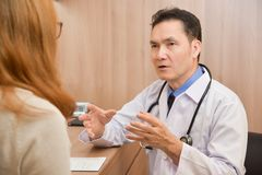 Asian Senior male Doctor discussing with female patient. stock photos