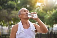 Asian senior male drinking water. Asian senior male drinking water after exercise at park outdoor background Royalty Free Stock Photo