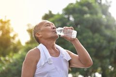 Asian senior male drinking water. Asian senior male drinking water after exercise at park outdoor background Royalty Free Stock Photos