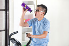 Asian senior male drinking water. On exercise bike Stock Photos