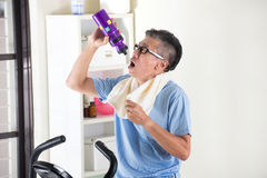 Asian senior male drinking water. On exercise bike Stock Photo