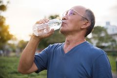 Asian senior male drinking water. Asian senior male drinking water after exercise at park outdoor background Royalty Free Stock Images
