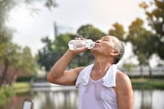 Asian senior male drinking water. Asian senior male drinking water after exercise at park outdoor background Stock Image