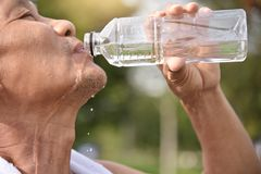 Asian senior male drinking water. Asian senior male drinking water after exercise at park outdoor background Stock Images