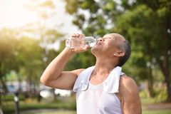 Asian senior male drinking water. Asian senior male drinking water after exercise at park outdoor background Stock Photo