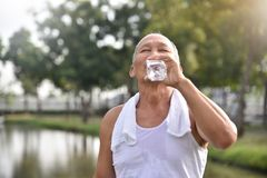 Asian senior male drinking water. Asian senior male drinking water after exercise at park outdoor background Stock Photos