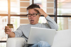 Asian senior male having trouble. Shopping online with credit card Stock Photos
