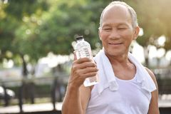 Asian senior male holding bottle of water. Asian senior male holding bottle of water for drinking while exercise at park outdoor background Stock Images