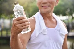Asian senior male holding bottle of water. Asian senior male holding bottle of water for drinking while exercise at park outdoor background Royalty Free Stock Images