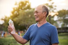 Asian senior male holding bottle of water. Asian senior male holding bottle of water for drinking while exercise at park outdoor background Stock Image