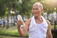 Asian senior male holding bottle of water. Asian senior male holding bottle of water for drinking while exercise at park outdoor background Stock Photos