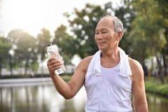 Asian senior male holding bottle of water. For drinking while exercise at park outdoor background Royalty Free Stock Photos