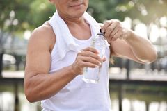 Asian senior male holding bottle of water. Asian senior male holding bottle of water for drinking while exercise at park outdoor background Royalty Free Stock Photography