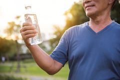 Asian senior male holding bottle of water. Asian senior male holding bottle of water for drinking while exercise at park outdoor background Stock Photography