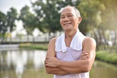 Asian Senior male posing with arms crossed. Confident Asian Senior male posing with arms crossed and smiling while exercising at park outdoor background Stock Photo