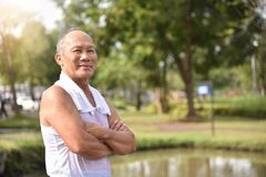 Asian Senior male posing with arms crossed. Confident Asian Senior male posing with arms crossed and smiling while exercising at park outdoor background Stock Photos