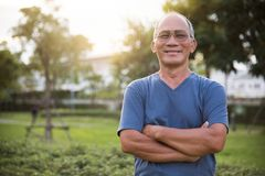 Asian Senior male posing with arms crossed. Confident Asian Senior male posing with arms crossed and smiling at park outdoor background Stock Photography