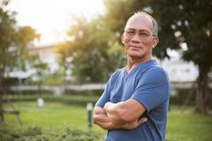 Asian Senior male posing with arms crossed. Confident Asian Senior male posing with arms crossed and smiling at park outdoor background Royalty Free Stock Photo
