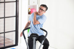 Asian senior male shoulder injury. On exercise bike Royalty Free Stock Image