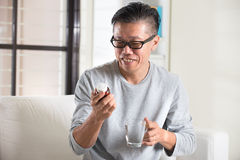 Asian senior male taking pills Royalty Free Stock Images