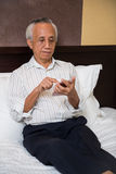 Asian senior male using technology. Asian senior sitting on bed learning new technology Royalty Free Stock Photos