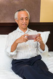 Asian senior male using technology. Asian senior sitting on bed learning to use new technology functions Stock Photography