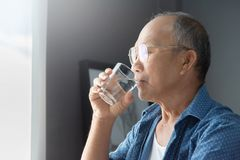 Asian Senior man drinking water. Asian Senior man in blue shirt drinking water Stock Photos