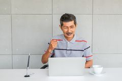 Asian senior man. with casual clothes. Rejoice,  raise fist right hand. Sitting look at to laptop computer screen. royalty free stock image