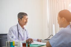 Asian Senior man doctor and patient sitting talking in hospital room. stock photography